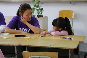 NYU Shanghai student Peiyao Wang (2021) chats with a student during the 2018 Rural Summer Camp.